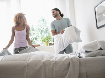 Young couple making bed in morning