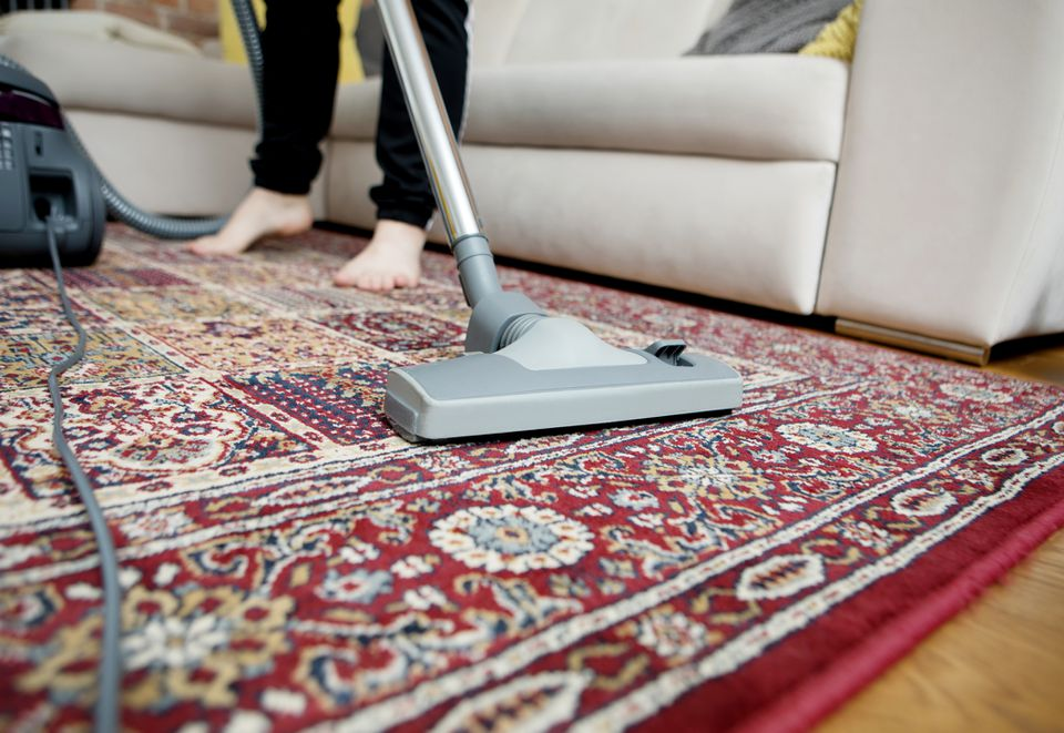 person vacuuming an antique rug