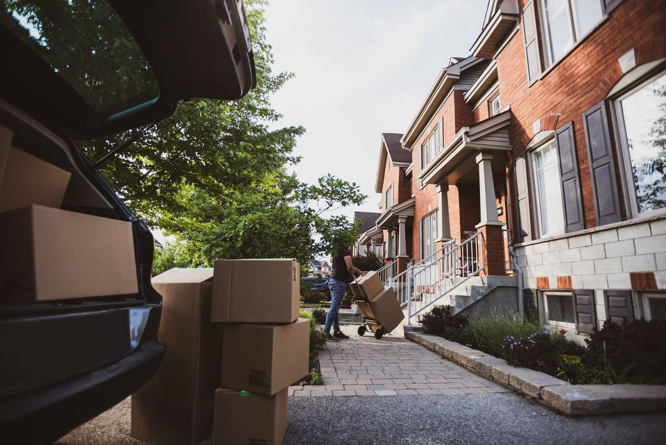 Young man carrying boxes from the car into the house
