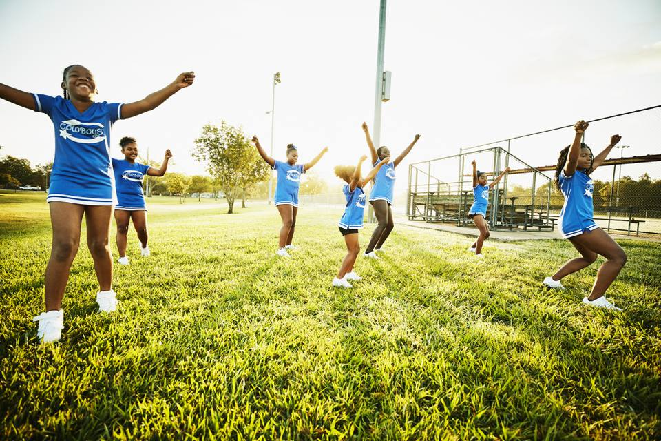 Young cheerleaders practicing routine in park during early morning workout