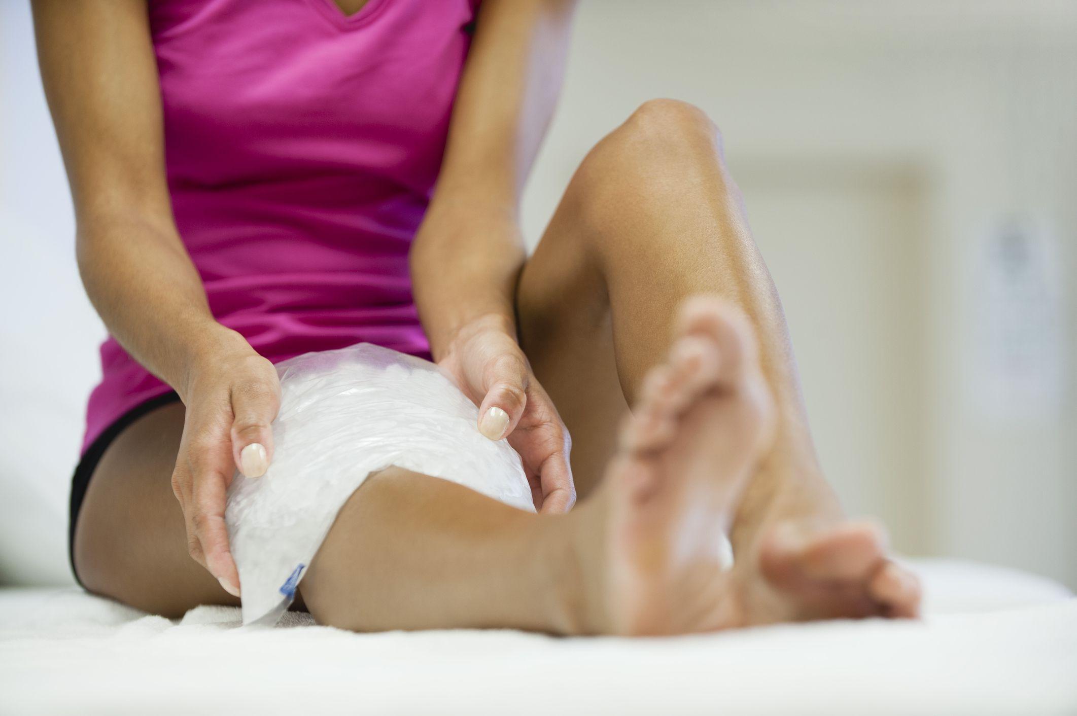 Mujer sentada con una bolsa de hielo en la rodilla derecha