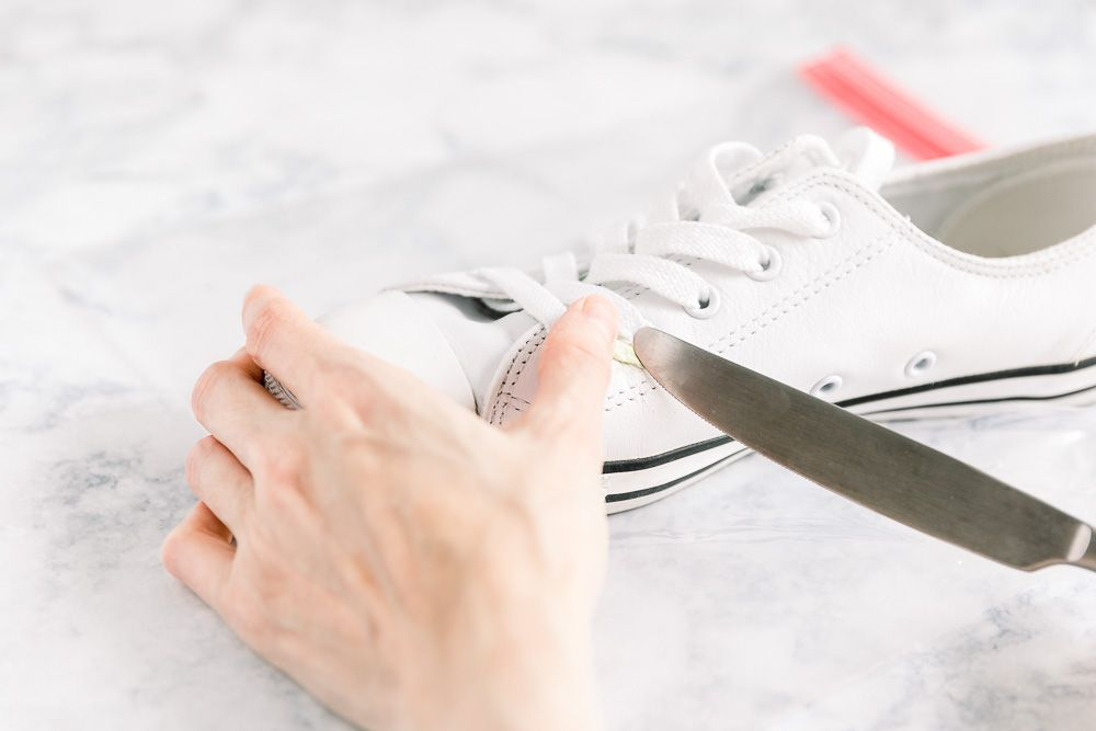 person scraping gum off of a shoe