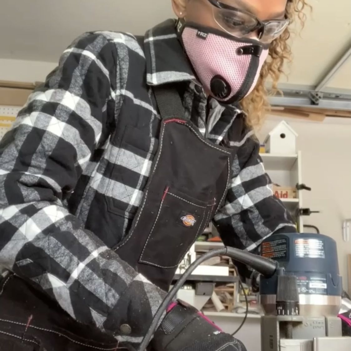 Char Miller-King works on wood, wearing a mask and eye protection