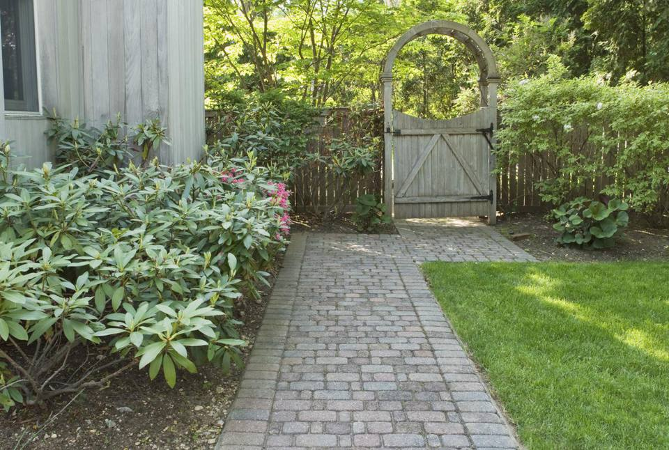 Brick walkway and wooden gate with arbor: image.