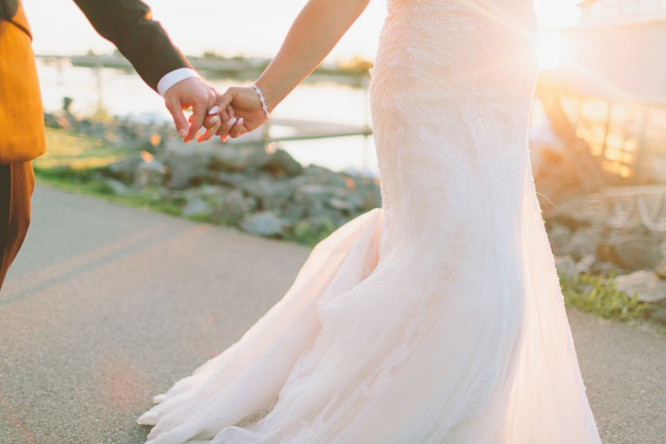 married couple walking hand in hand at sunset
