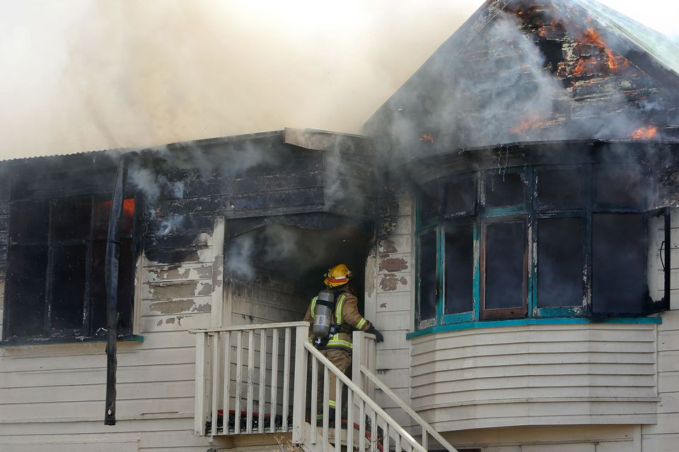 Firefighter battling a house fire