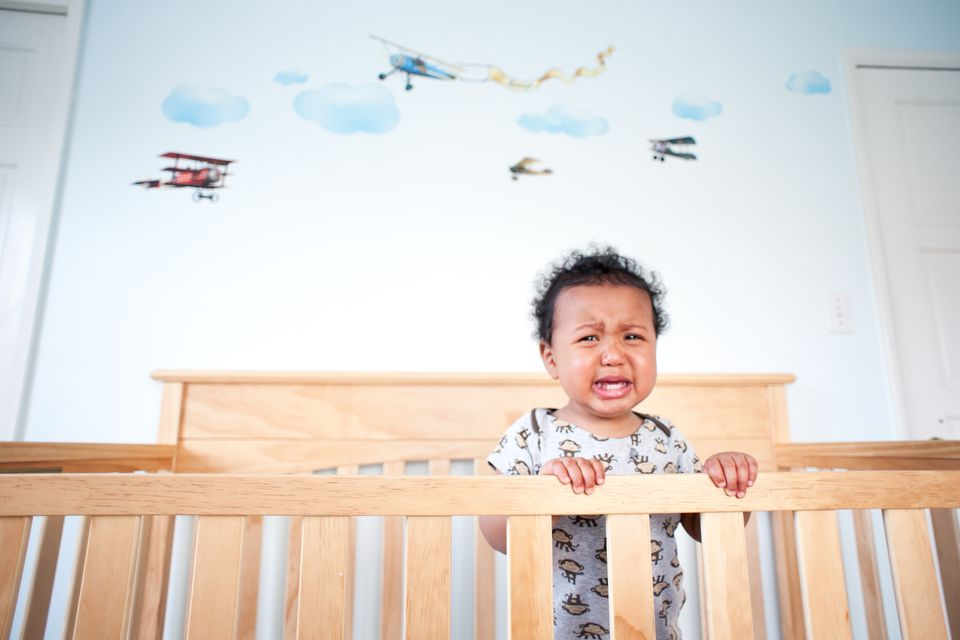 Standing toddler boy crying in the crib