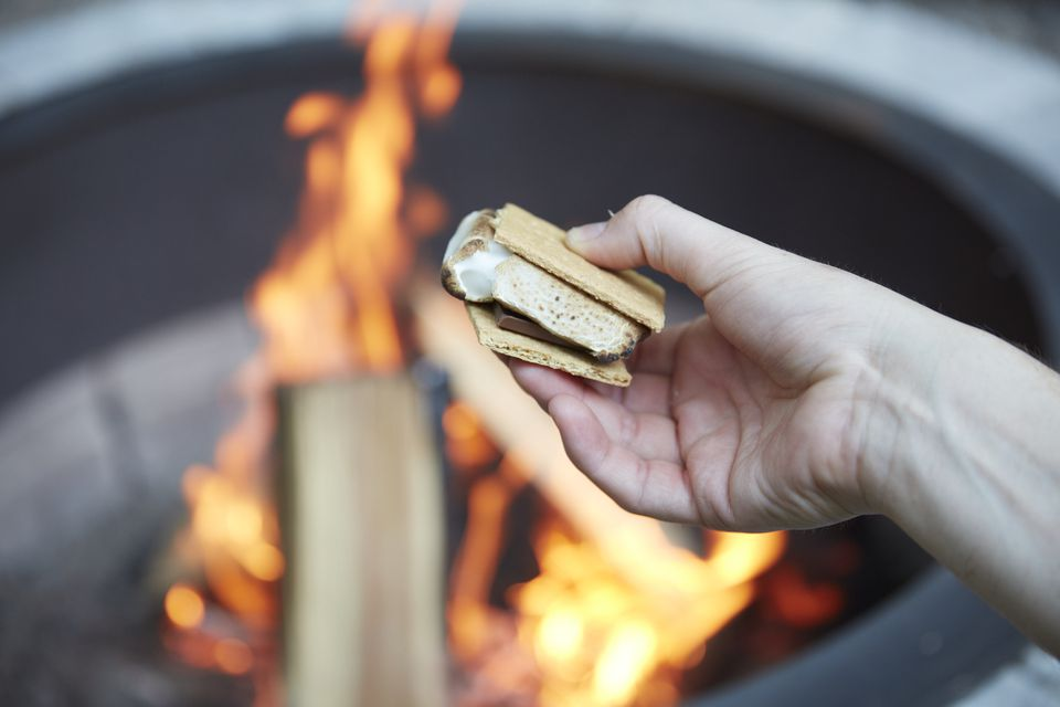 Smores held in hand over fire in firepit