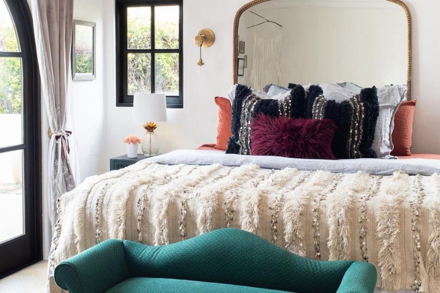 modern bedroom, green bench at end of bed, mirror as headboard, triadic colors