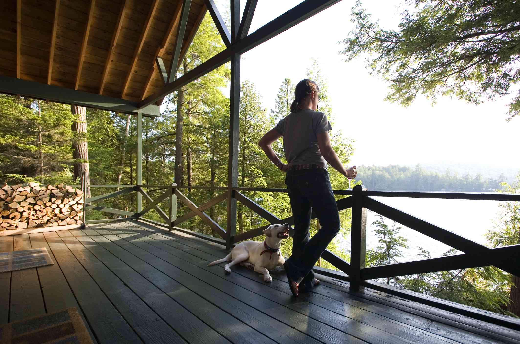 woman on log cabin deck near lake