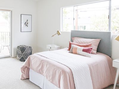 Light-filled bedroom with cream-colored carpet below bed with pink bedding