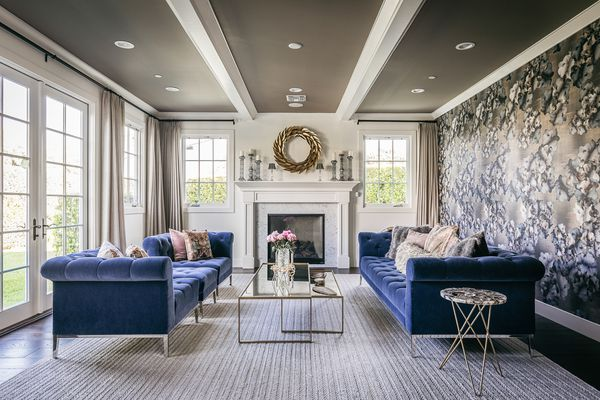 Living room with blue velvet couches elegantly decorated with metal and glass furniture with large windows