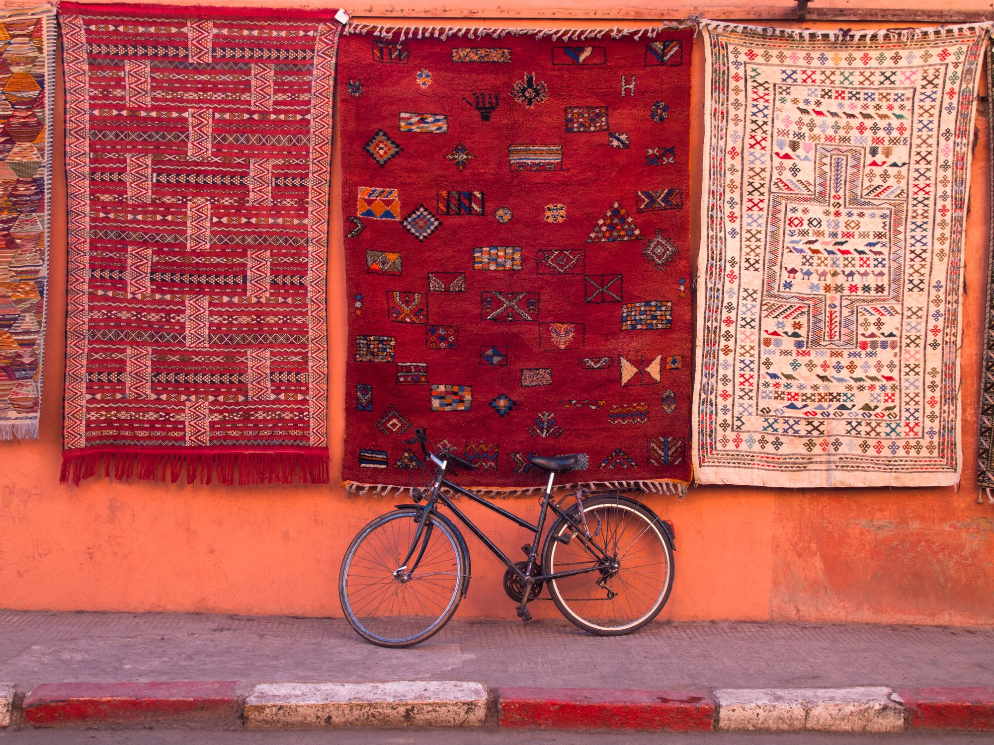 Bicycle parked at wall under hanging carpets with traditional patterns.