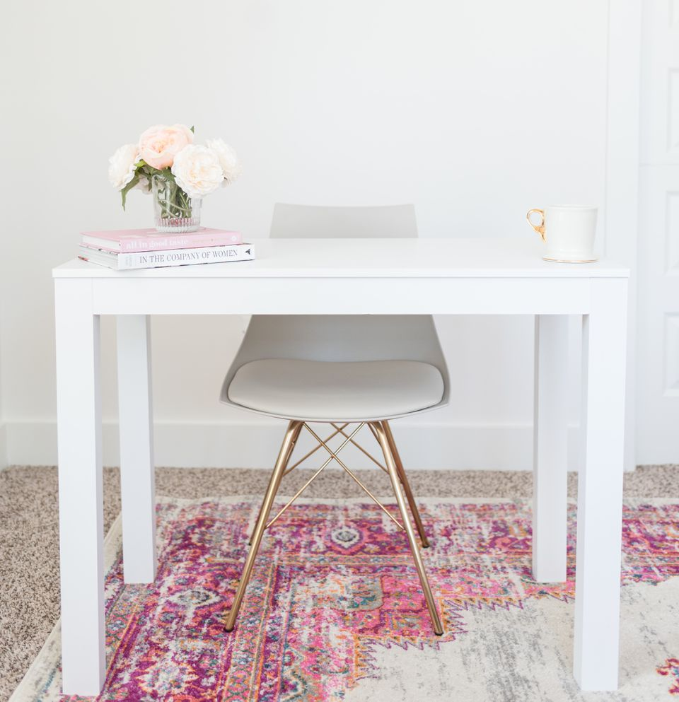 Desk and chair atop rug on carpet