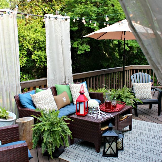 A deck with diy curtains and patio furniture