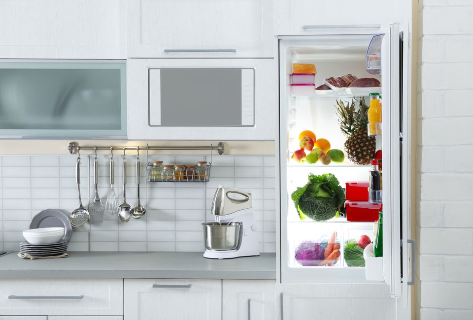 Open refrigerator full of products in stylish kitchen interior