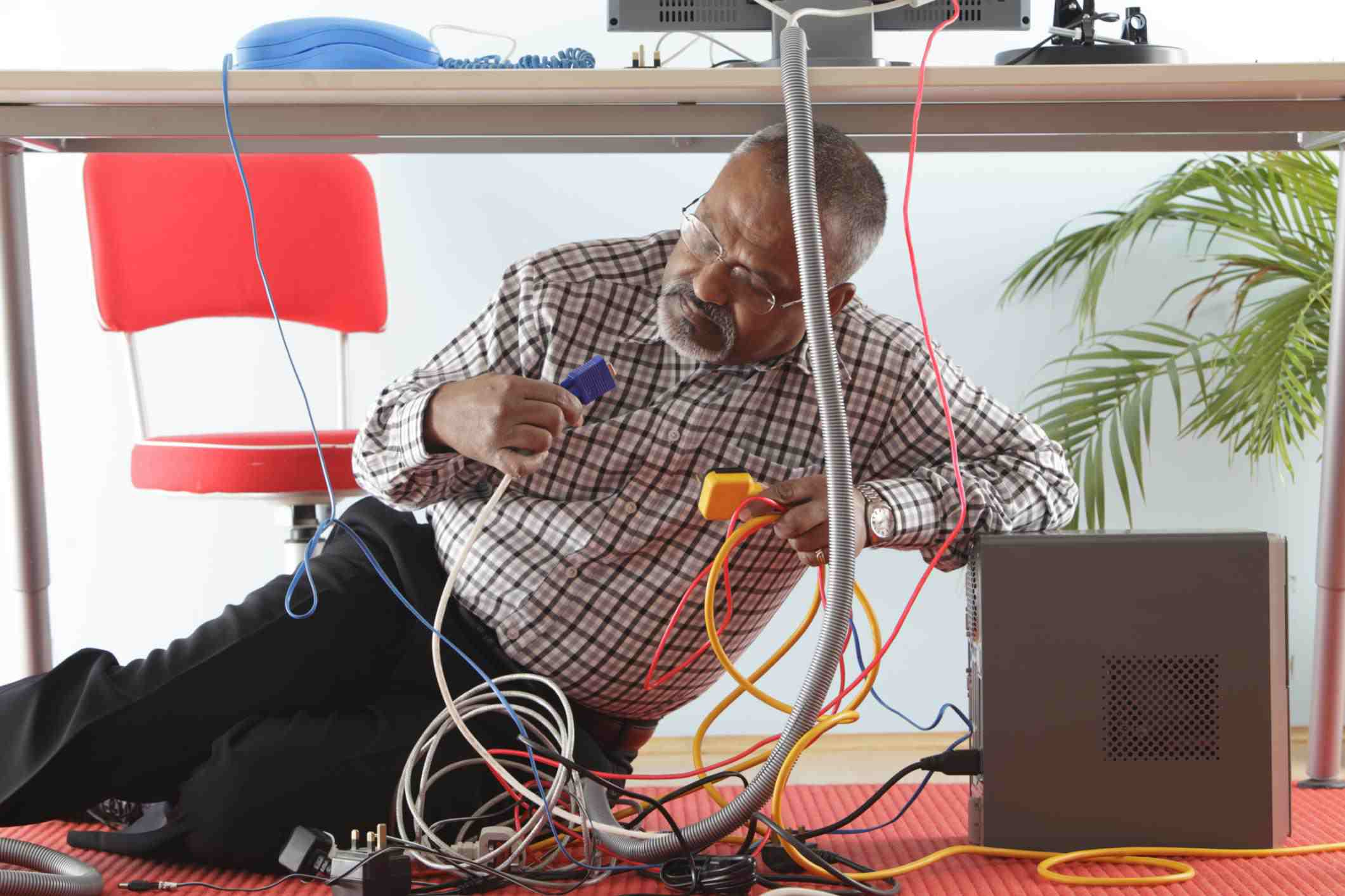 Man under desk with computer wires