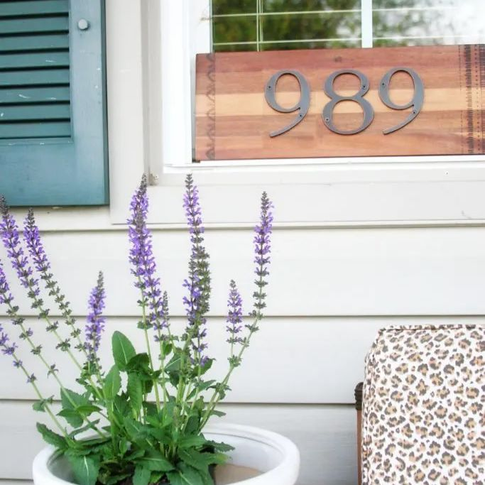 A wooden number sign on a window sill in front of a lavender plant.