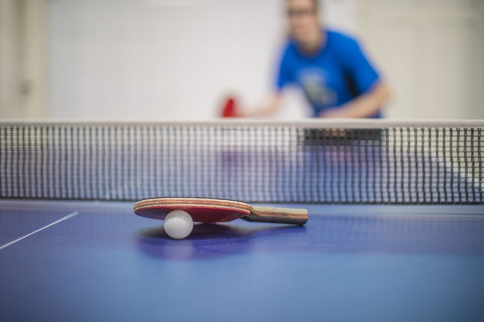 Ping pong paddle and ball on a table