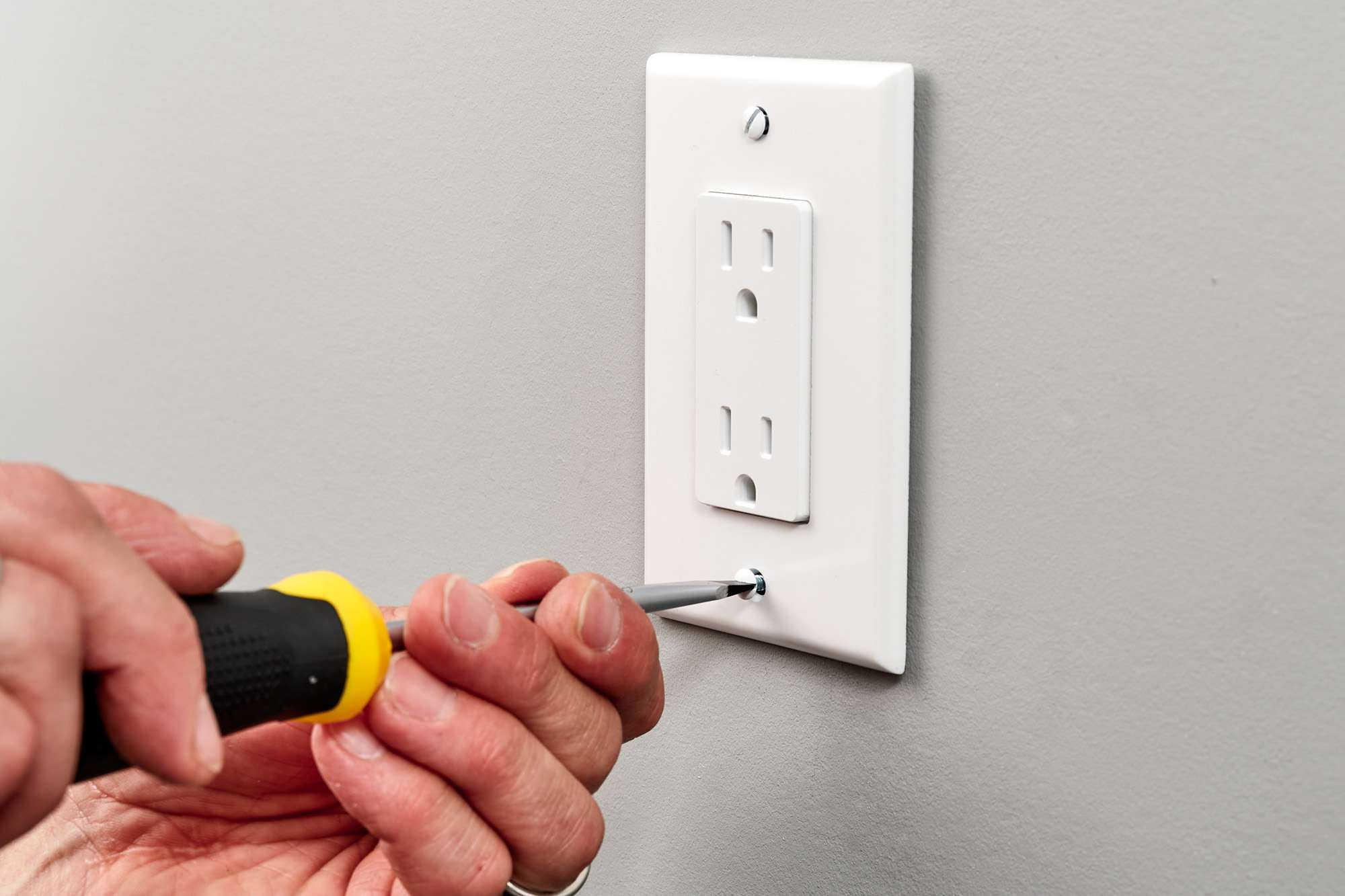 Outlet cover plate installed with screwdriver
