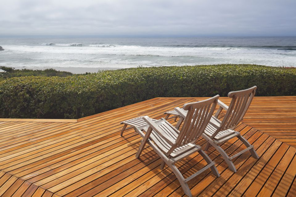 Lounge chairs on a wooden deck by the ocean