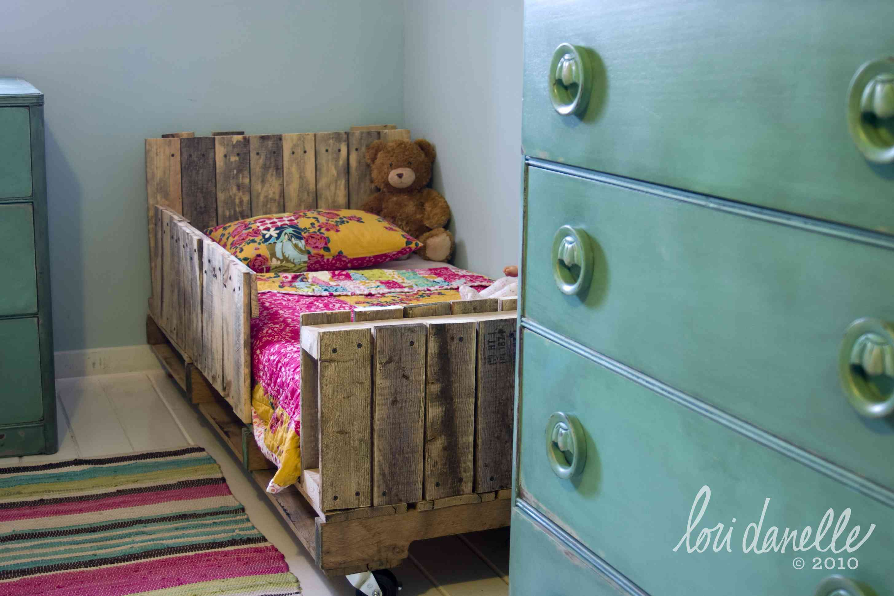 A toddler bed made out of pallets by a green dresser