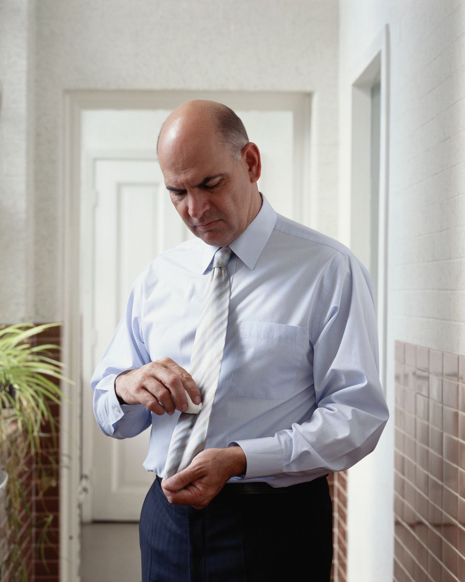 Businessman cleaning tie with cloth, frowning