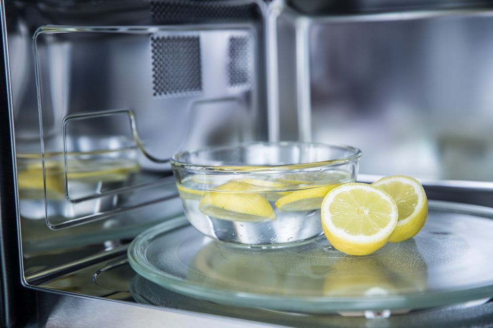 Sliced lemons in a clear glass inside stainless steel microwave