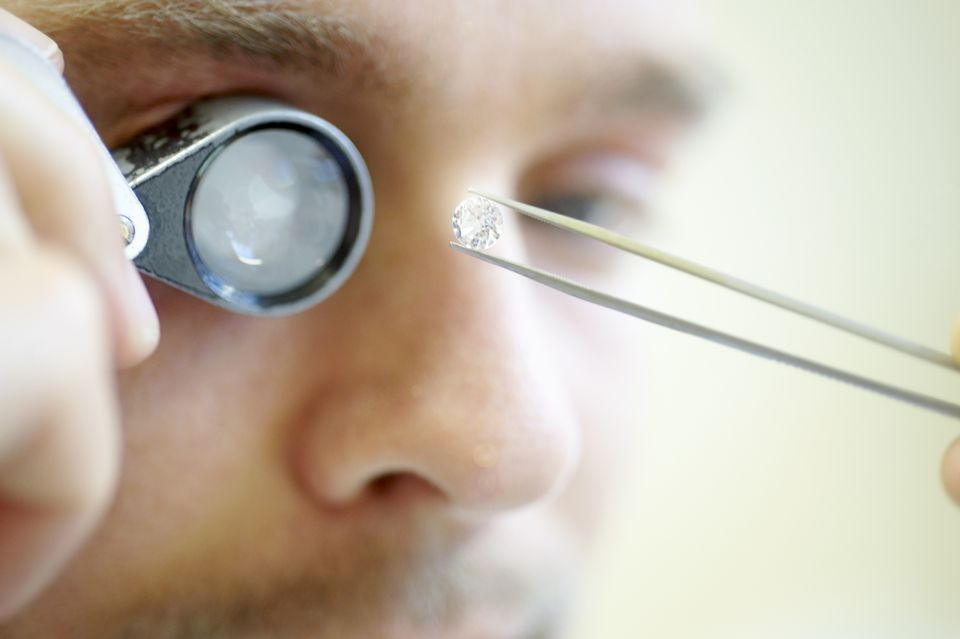 A man examining a diamond with a jewler's loupe