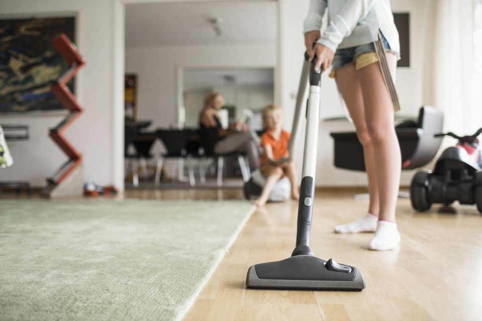 Woman vacuuming floor with kids in background