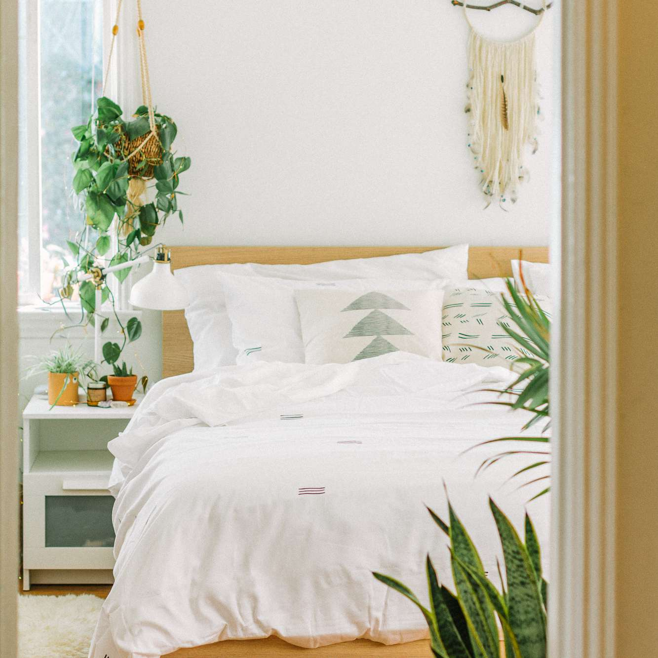 Bedroom with lots of plants and white bedding