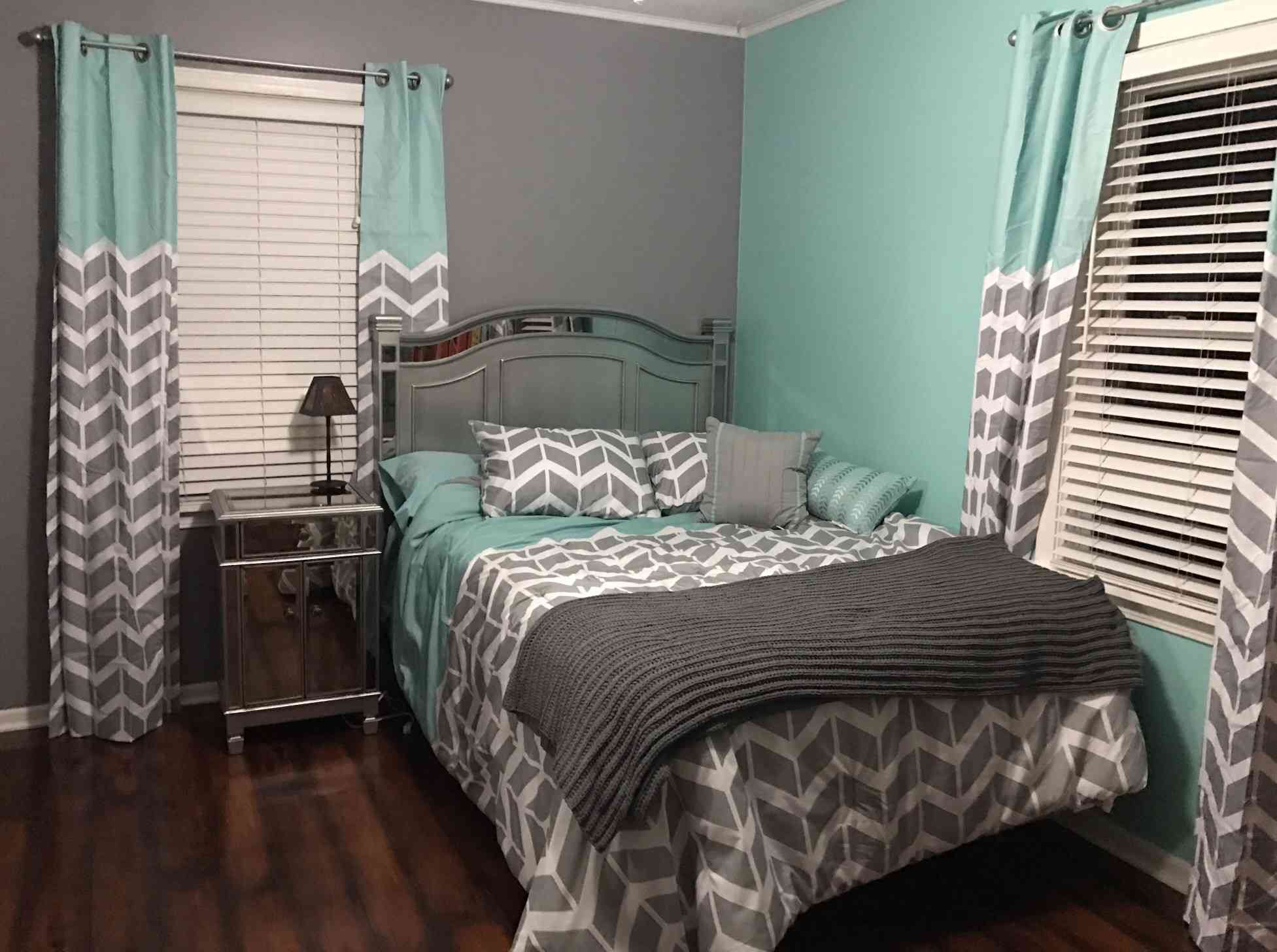 Chevron bedspread and curtains in a gray and teal bedroom.