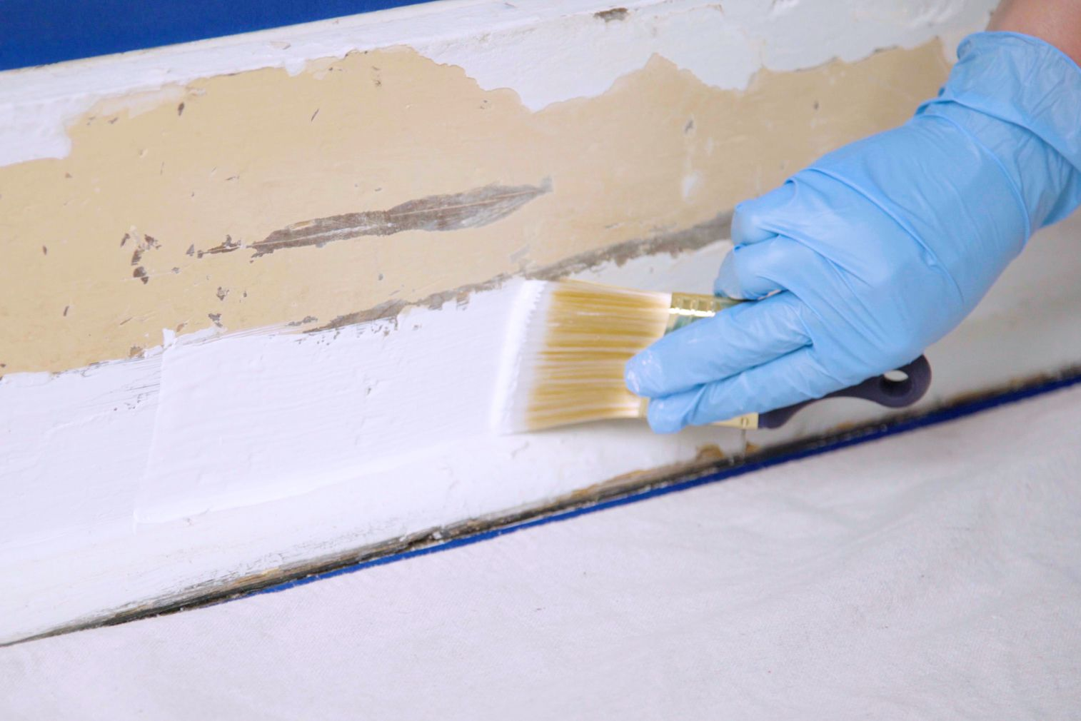 Baseboard lightly primed with white primer coat with blue gloves