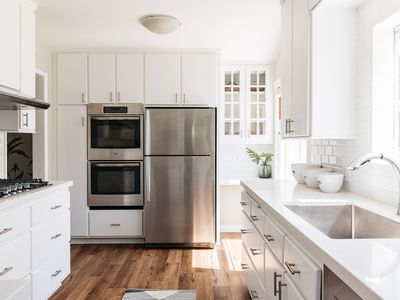 Brightly-lit kitchen with quartz countertops and white cabinets and stainless steel appliances
