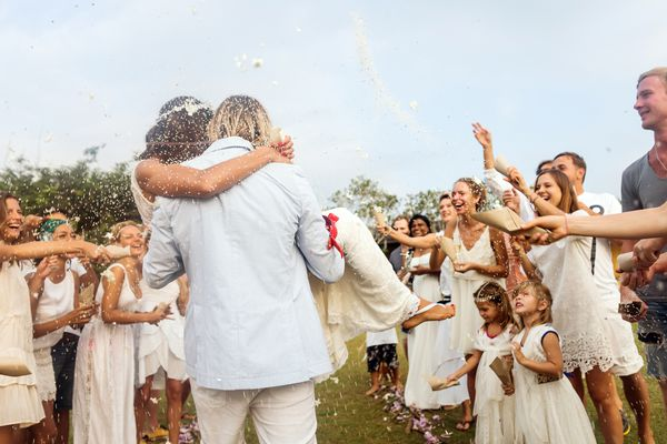 Wedding guests tossing rice at bride and groom
