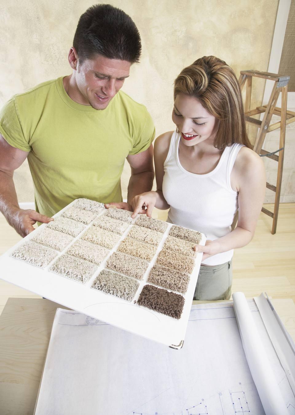 Couple choosing carpet sample with blueprints