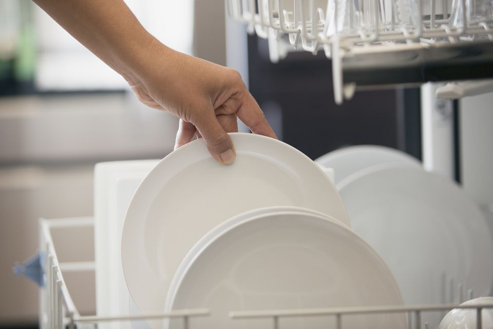 Close-up of woman unloading white dishes from dishwasher.