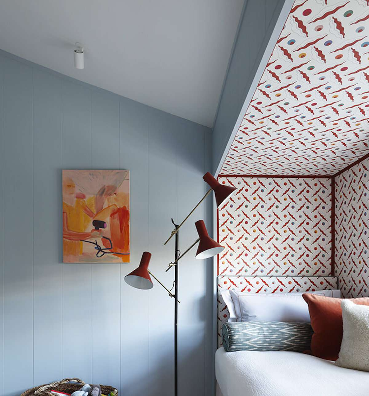bedroom with pale blue walls, red and white pattern in nook containing a bed, modern red lamp