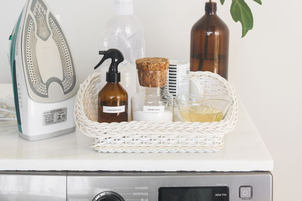An iron and laundry products on top of a washer or dryer