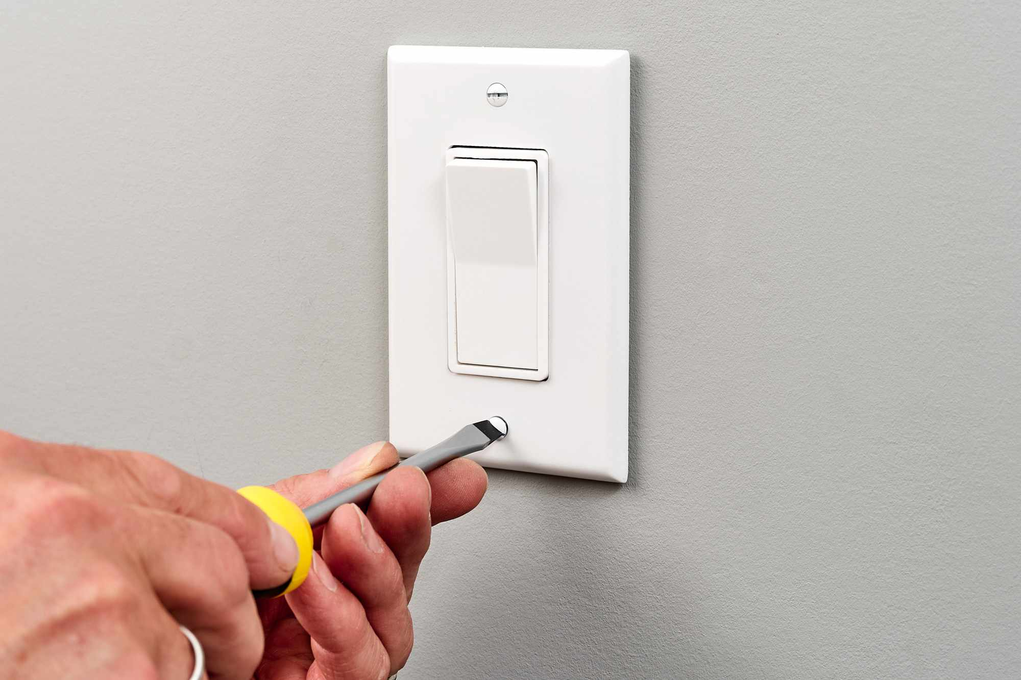 Single-pole switch faceplate installed with screwdriver