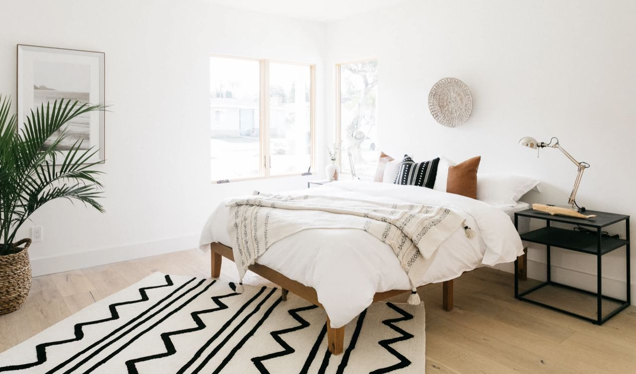 minimalist bedroom with wooden bed frame, large plant in corner