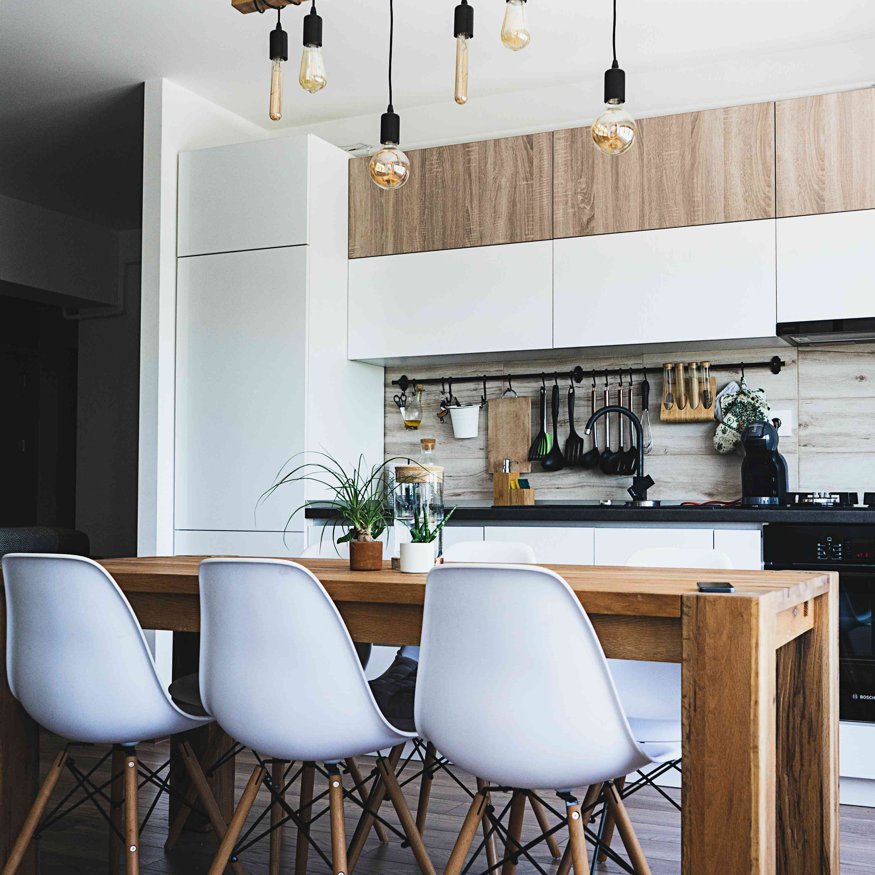 modern kitchen with wood and white cabinets and dining table