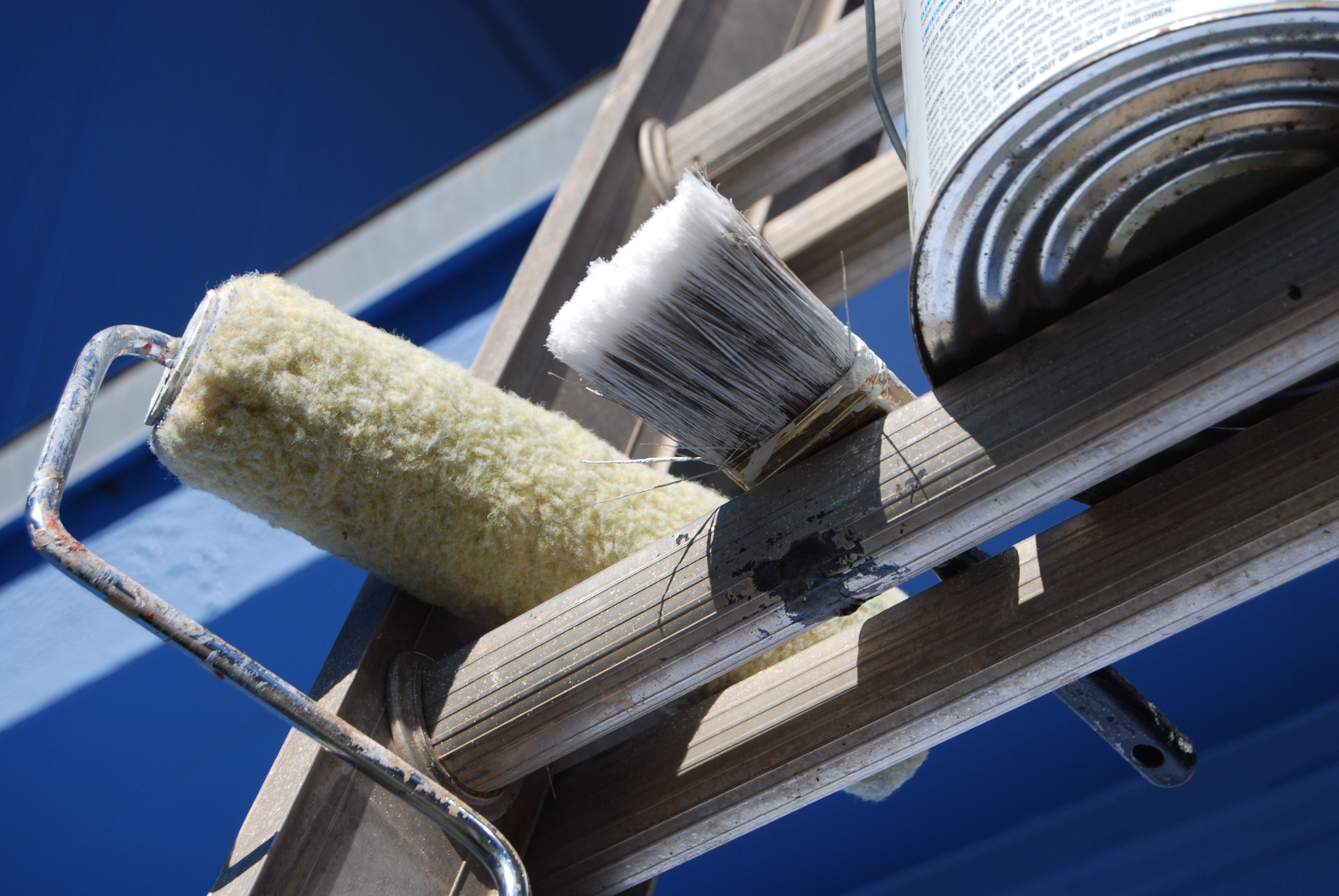 Paint-roller, Paintbrush, and paint-can on ladder