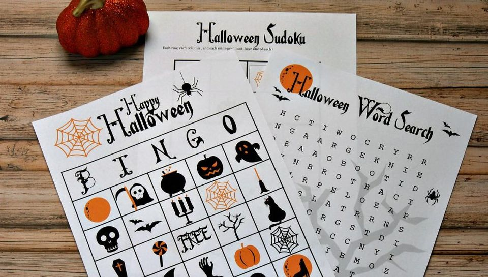 Halloween bingo cards and other games on a table