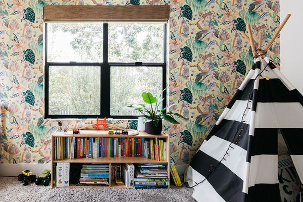 Wallpapered kids playroom with black and white striped teepee and bookshelf underneath window