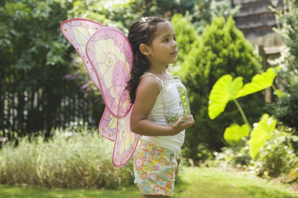 Child wearing butterfly wings and holding a jar.