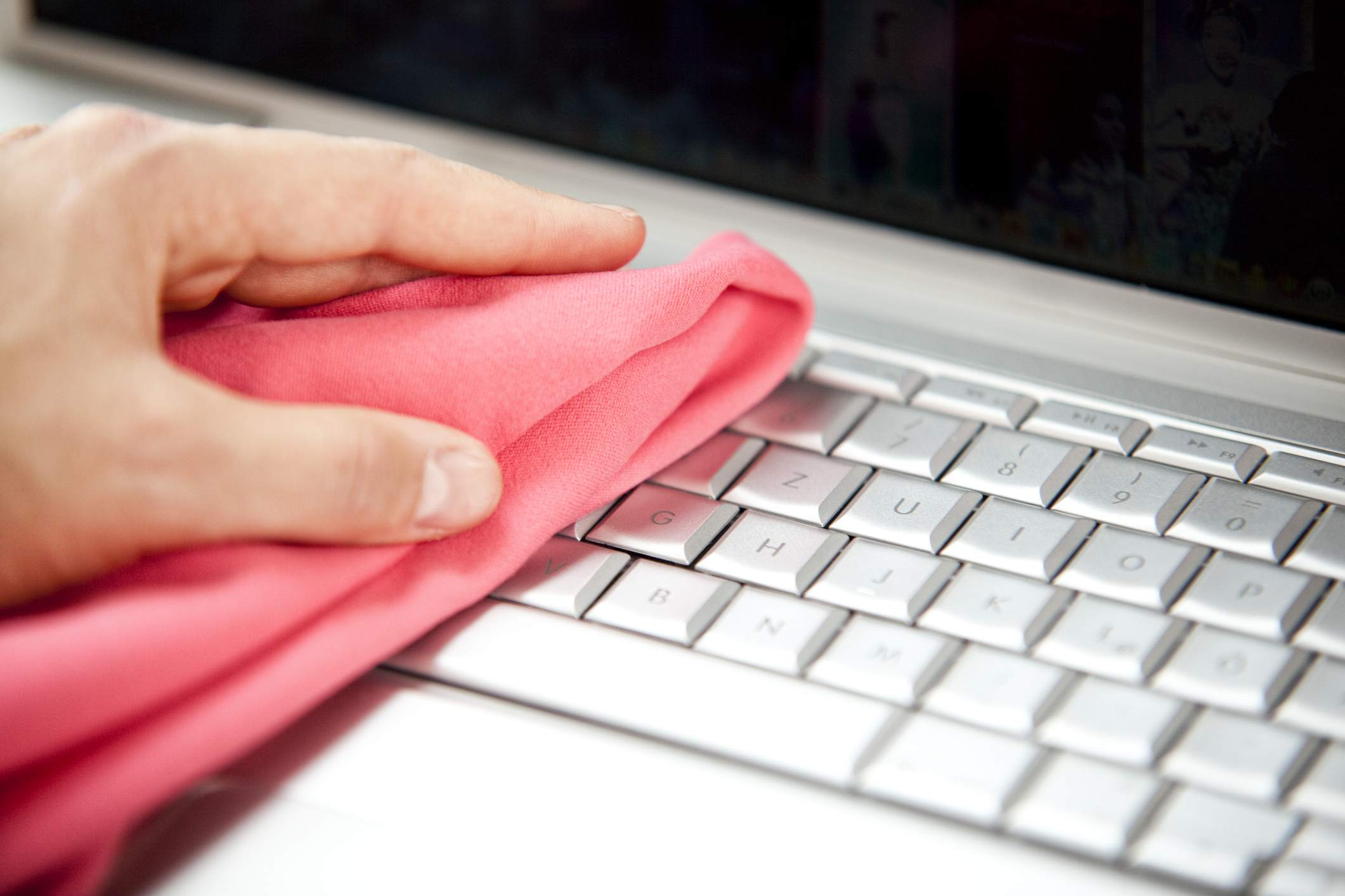 Mujer limpiando la computadora portátil con un plumero rojo