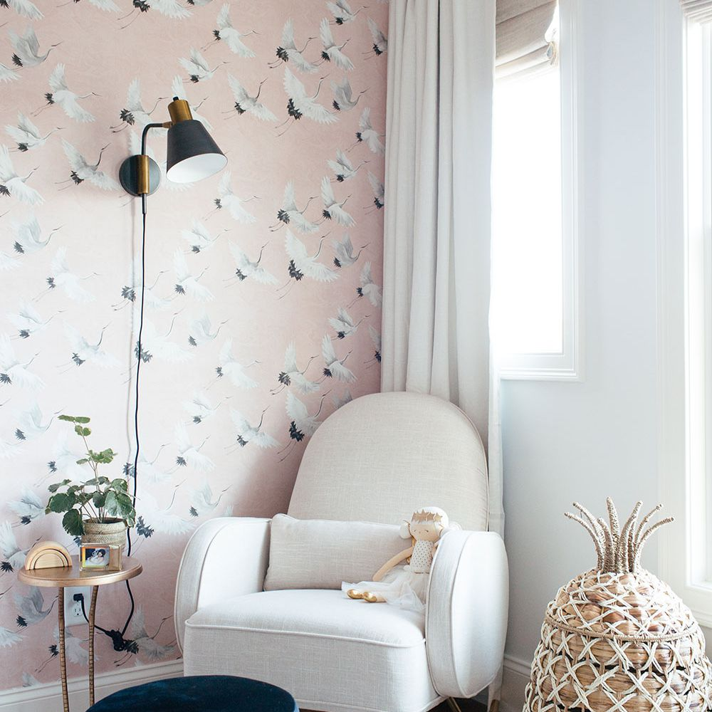 nursery with pink crane wallpaper accent wall, black sconce, white rocking chair with wicker pineapple basket