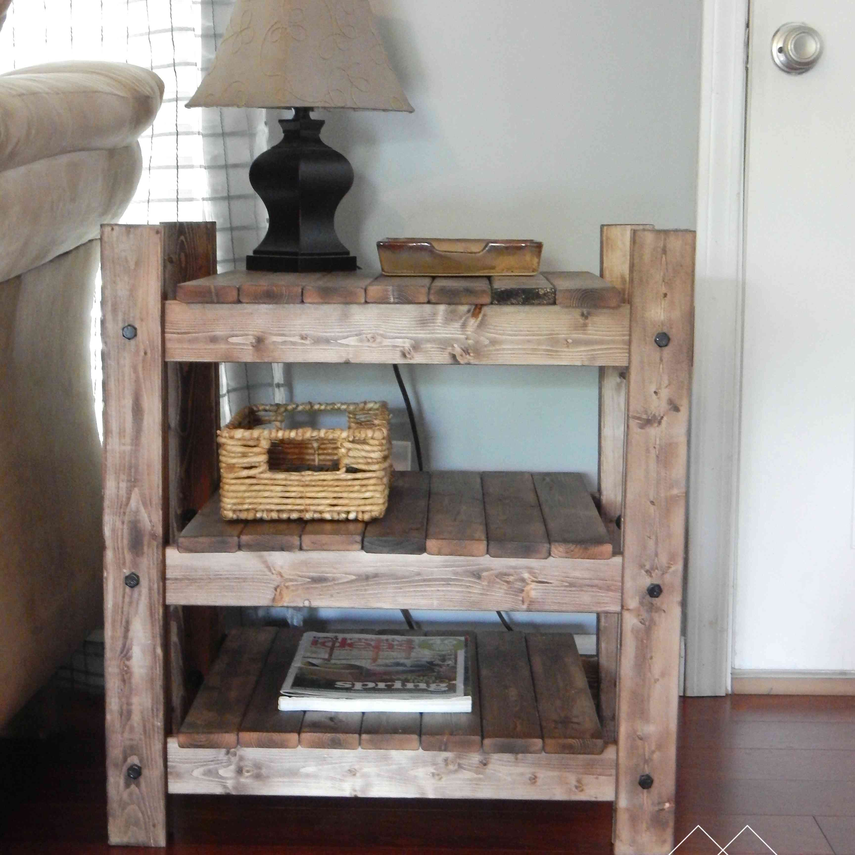 An end table with a lamp, basket, and book on it