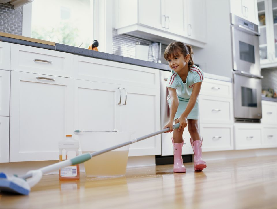 Low-angle view of girl cleaning kitchen floor.